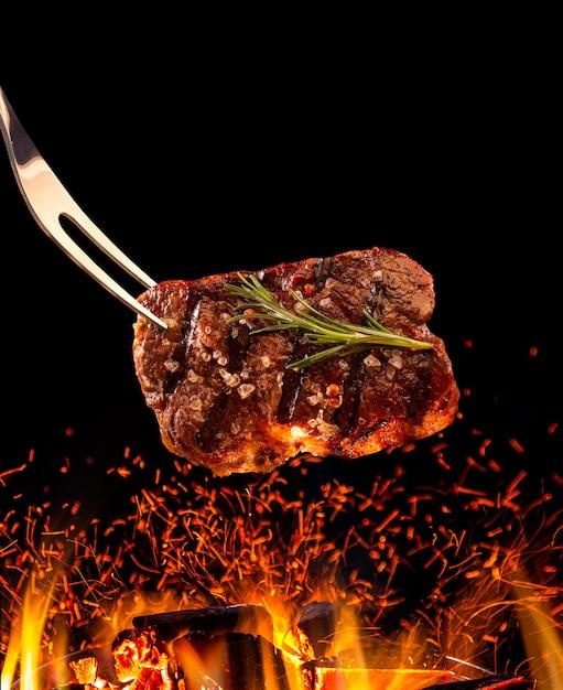 Stek Wołowy Spada Na Grill Z Ogniem. Premium Zdjęcia