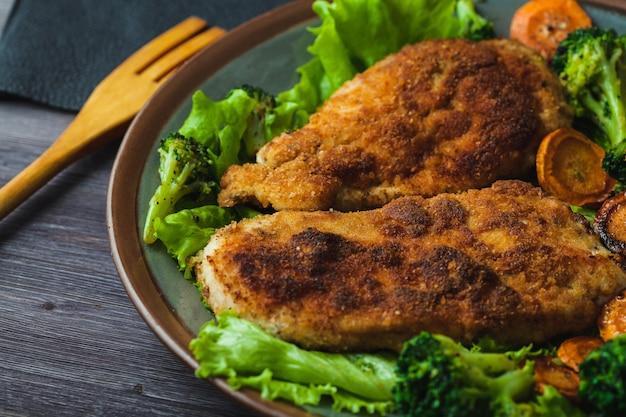 Stek Z Kurczaka W Bułce Tartej Z Warzywami Na Talerzu Premium Zdjęcia