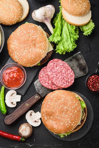 Steki Wołowe Mielone I Dwa Hamburgery Na Czarnym Tle, Leżał Na Płasko Premium Zdjęcia