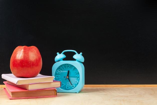 Sterta książki z jabłkiem i ołówkiem na stole Premium Zdjęcia