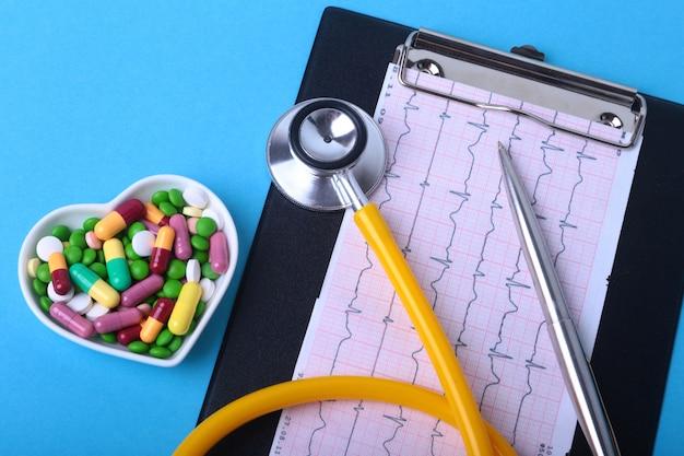 Stetoskop, rx na receptę i kolorowe pigułki asortymentowe i kapsułki na talerzu. Premium Zdjęcia