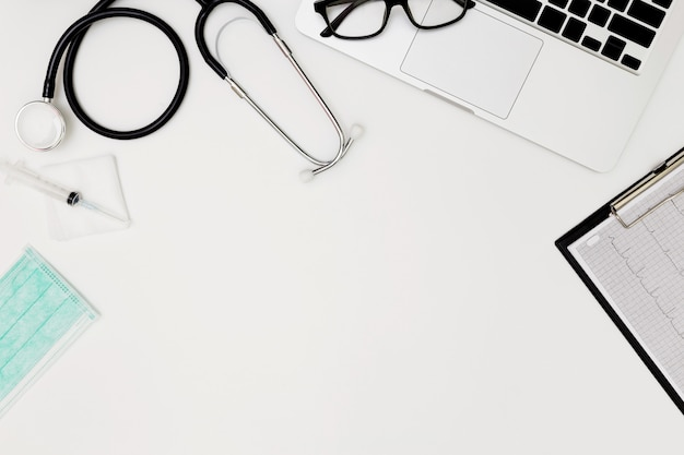 Stetoskop, Widok Z Góry Stolika Lekarskiego, Czysty Papier Na Białym Tle, Powyżej Widok Narzędzia Pracy Lekarza Na Białym, Stetoskop, Laptop, Okulary I Lek Na Białym Tle, Lekarz Premium Zdjęcia