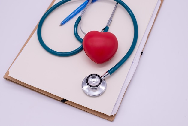 Stetoskop z czerwonym sercem i prześcieradło deska na białym tle Premium Zdjęcia