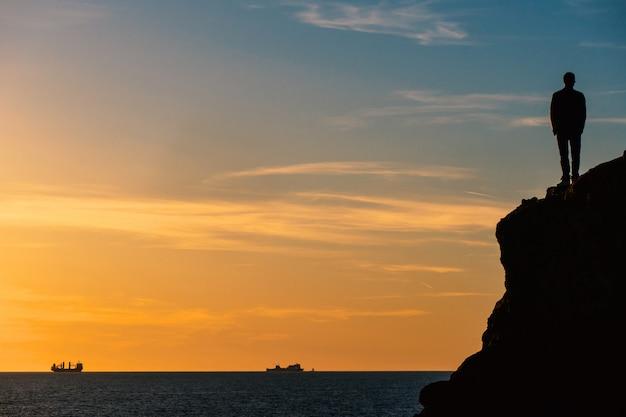 Stojący Mężczyzna Silouette Na Skale Przed Morzem Przy Zmierzchem Premium Zdjęcia