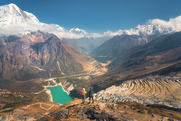 Stojący Mężczyźni Z Plecakami Na Szczycie Góry I Patrząc Na Piękną Górską Dolinę O Zachodzie Słońca. Premium Zdjęcia