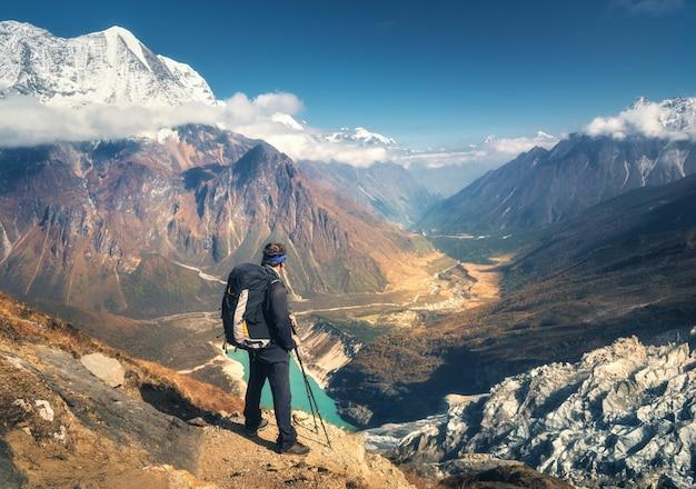 Stojący Sportowy Mężczyzna Z Plecakiem Na Szczycie Góry I Patrząc Na Piękną Górską Dolinę O Zachodzie Słońca Premium Zdjęcia