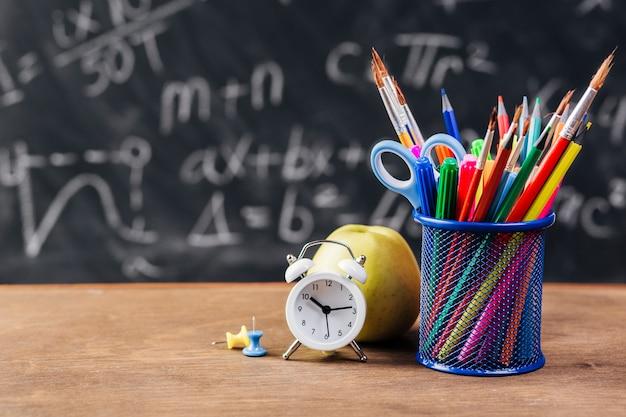 Stojak z rysunkowymi narzędziami i budzikiem na chalkboard tle Darmowe Zdjęcia