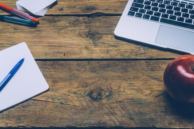Stół biurowy z laptopem, piórami, notatnikiem i jabłkiem. Premium Zdjęcia