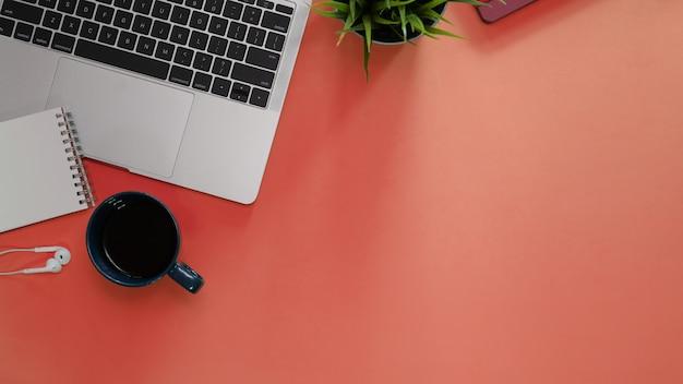 Stół Biurowy Z Materiałów Biurowych I Laptopa Na Pomarańczowym Tle Premium Zdjęcia