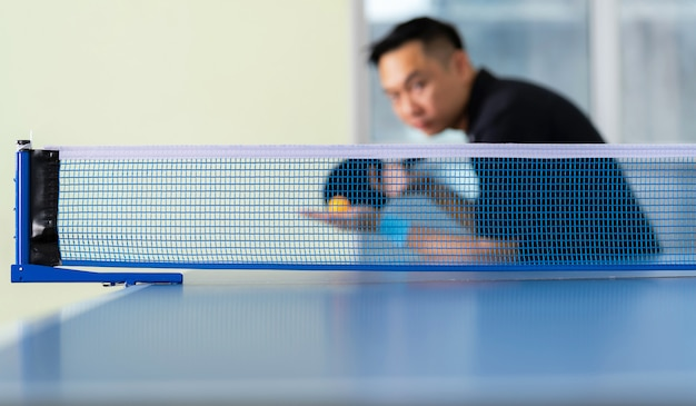 Stół do ping-ponga, mężczyzna grający w tenisa stołowego z rakietą i piłką w hali sportowej Premium Zdjęcia