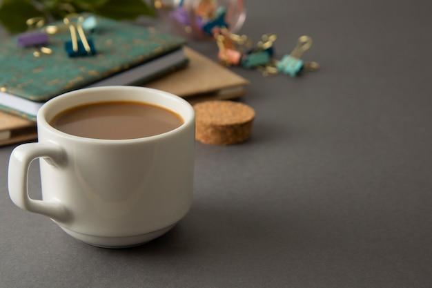 Stół Roboczy Z Notatnikami, Artykułami Biurowymi I Filiżanką Kawy. Szare Tło. Przestrzeń Robocza. Premium Zdjęcia