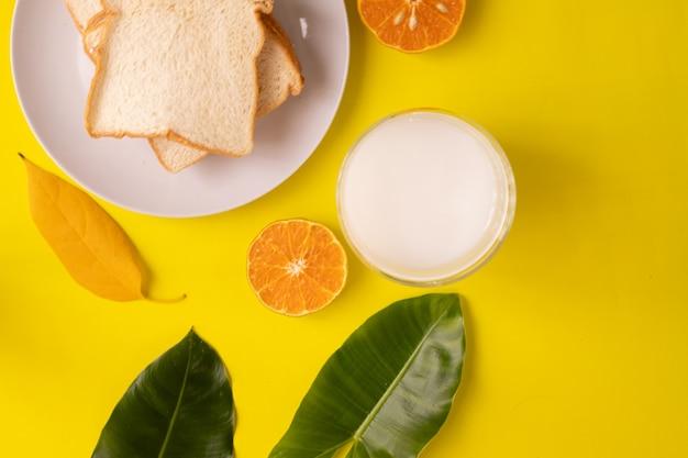 Stół śniadaniowy Z Krojonym Chlebem I Szklanką Mleka Na żółto Premium Zdjęcia