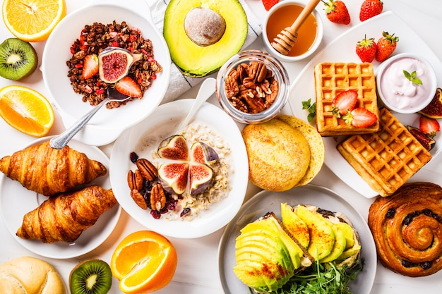 Stół śniadaniowy z tostem z awokado, płatkami owsianymi, goframi, rogalikami na białym tle Premium Zdjęcia