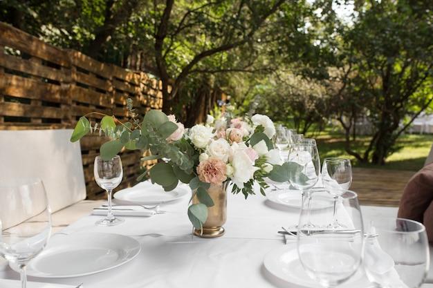 Stół weselny ozdobiony świeżymi kwiatami w mosiężnym wazonie Premium Zdjęcia