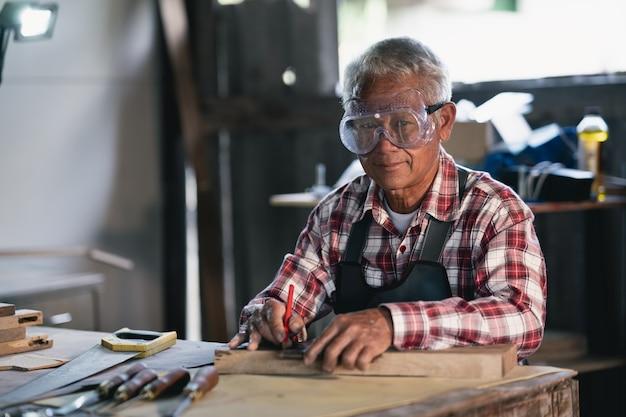 Stolarz Pracuje Na Drewnie W Stolarni. Mężczyzna Pracuje W Stolarni Premium Zdjęcia