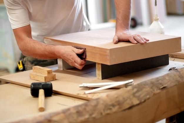 Stolarz Ręcznie Szlifuje Drewniany Klocek Premium Zdjęcia