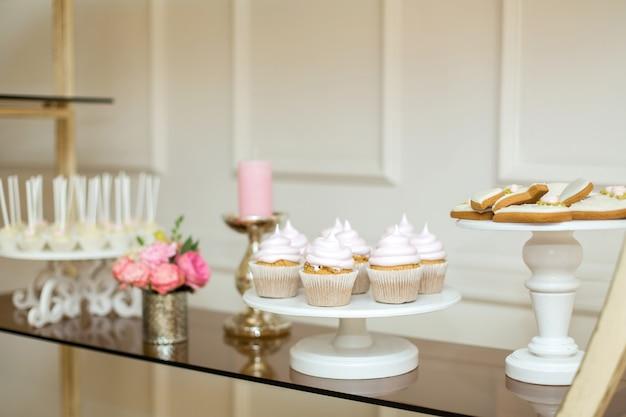 Stolik Okolicznościowy Ze Słodyczami, Minimalnie Ozdobiony świeżymi Kwiatami Premium Zdjęcia