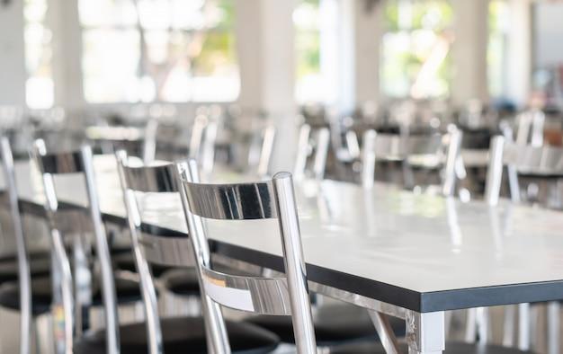 Stoły i krzesła ze stali nierdzewnej w stołówce dla uczniów szkół średnich Premium Zdjęcia