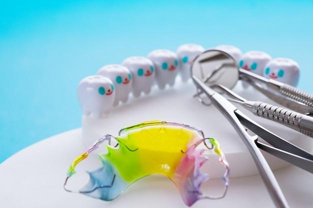 Stomatologicznego elementu ustalającego ortodontyczny urządzenie i stomatologiczni narzędzia na błękitnym tle. Premium Zdjęcia