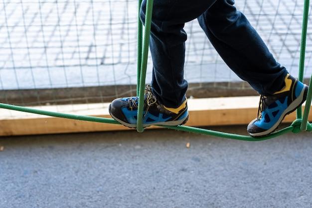 Stopa dziecko robi równowagi na drewnianych deskach w miejskim parku rozrywki. Premium Zdjęcia