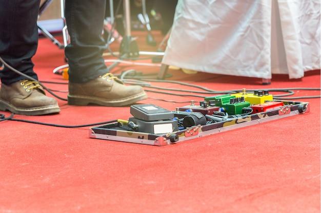 Stopy gitarzysty na scenie z zestawem pedałów efektu zniekształceń. selektywne skupienie Premium Zdjęcia