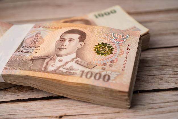 Stos Banknotów Bahtów Tajskich Na Drewnianych. Premium Zdjęcia