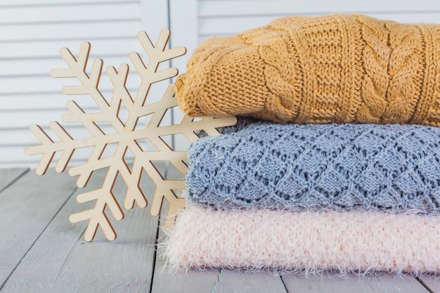 Stos Białe Przytulne Swetry Z Dzianiny Na Drewnianym Stole Premium Zdjęcia