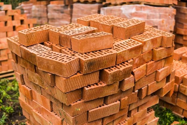 Stos Czerwonej Cegły Dla Budowy. Cegły Budowlane Zwykłej Jakości Ułożone W Stos I Gotowe Do Użycia. Premium Zdjęcia