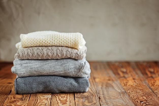 Stos Dzianin Zimowych Ubrań Na Drewnianych Sweterkach Premium Zdjęcia