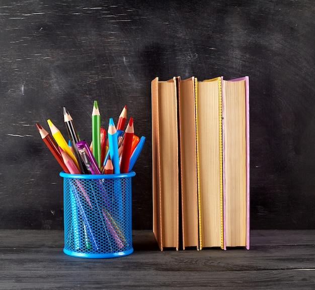 Stos Książek I Niebieskie Szkło Biurowe Z Wielobarwnymi Drewnianymi Ołówkami Premium Zdjęcia