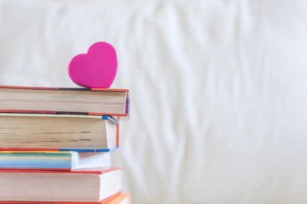 Stos książek i różowe serce na białym łóżku Premium Zdjęcia