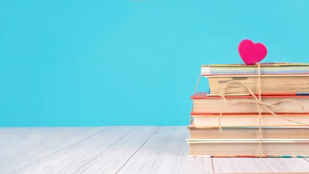 Stos książek i różowe serce Premium Zdjęcia