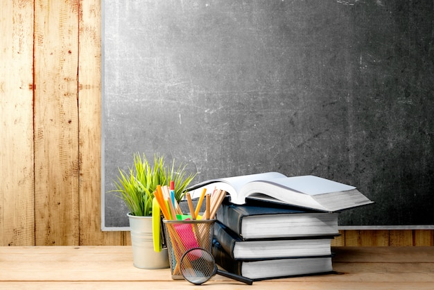 Stos książek z roślin doniczkowych i ołówki w pojemniku kosz z lupą na drewnianym stole Premium Zdjęcia