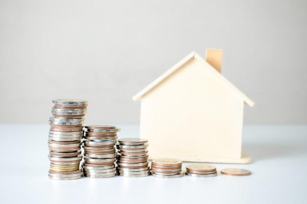 Stos monet i plany domów. inwestycje w nieruchomości i hipotekę finansową. Premium Zdjęcia