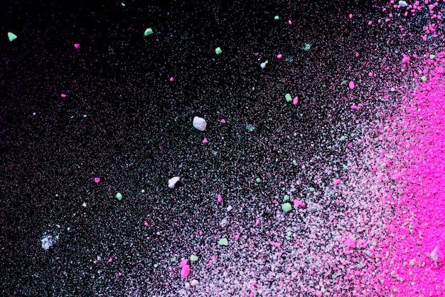 Stos naturalnego barwnego proszku pigmentowego. rozpryskiwają się cząsteczki zielonego różowego białego proszku Premium Zdjęcia