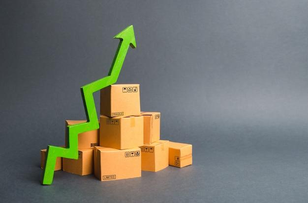Stos pudeł kartonowych i zielona strzałka w górę. tempo wzrostu produkcji towarów i produktów Premium Zdjęcia