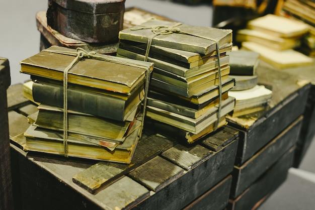 Stos starych książek przechowywanych w ruinę na starym bagażniku vintage. Premium Zdjęcia