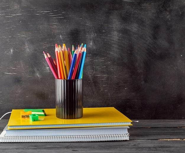 Stos Zeszytów, Czarne Szkło Biurowe Z Wielobarwnymi Drewnianymi Ołówkami Premium Zdjęcia