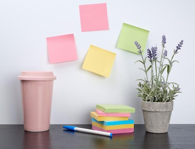 Stos zeszytów i kolorowych naklejek obok ceramicznej doniczki z kwiatkiem Premium Zdjęcia