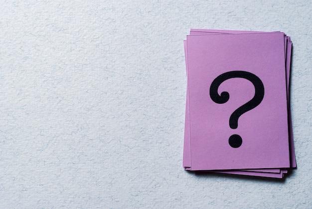 Stos znaków zapytania na purpurowym papierze Premium Zdjęcia