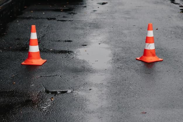 Stożek drogowy, z biało-pomarańczowymi paskami na szarym asfalcie Premium Zdjęcia