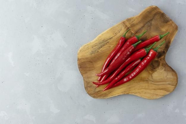 Strąki świeżych Gorących Chili Pieprzy Kłamają Na Drewnianej Desce Na Szarym Tle. Przyprawa Meksykańska. Miejsce Na Twój Tekst. Premium Zdjęcia