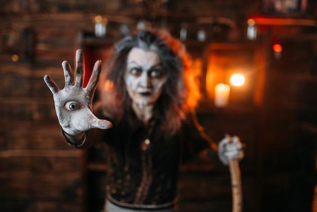 Straszna Wiedźma Z Okiem W Dłoni Czyta Mistyczne Zaklęcie, Seans Duchowy. Kobieta Wróżbita Nazywa Duchy, Straszną Wróżbitą Premium Zdjęcia