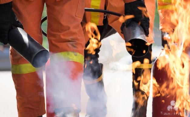 Strażak Próbuje Zatrzymać Ogień Przez Gaśnicę W Szkoleniu Przeciwpożarowym. Premium Zdjęcia