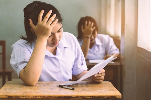 Stres dziewczyna uczeń czyta i pisze egzamin Premium Zdjęcia
