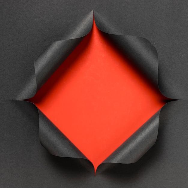 Streszczenie Czerwony Kształt Na Podartym Czarnym Papierze Darmowe Zdjęcia