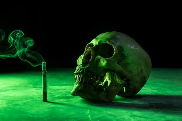 Streszczenie martwa natura czaszka szkieletu z płonącym papierosem, przestań palić kampanię z copyspace. Premium Zdjęcia