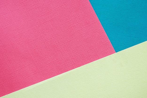 Streszczenie tło i tekstura. trzy arkusze różnokolorowego różowego, niebieskiego i jasnożółtego papieru z fakturą. Premium Zdjęcia