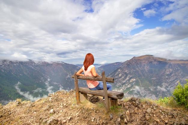 Strój przypadkowej kobiety. czerwona włosiana dziewczyna relaksuje na ławce cieszy się naturę nad góra widoku krajobraz. travel lifestyle przygoda wakacje na świeżym powietrzu. czarnogóra Premium Zdjęcia