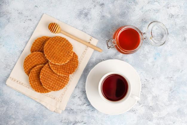 Stroopwafels, Karmelowe Holenderskie Gofry Z Herbatą Lub Kawą I Miodem Na Betonie Darmowe Zdjęcia